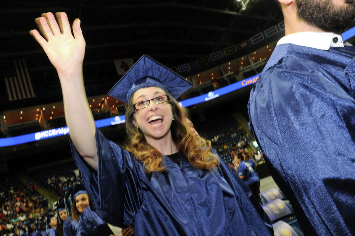 Alegre Poniros, of Bridgeport, waves to family as she enters Commencement for the Housatonic Community College graduating Class of 2018 at the Webster Bank Arena, in Bridgeport, Conn. May 24, 2018.