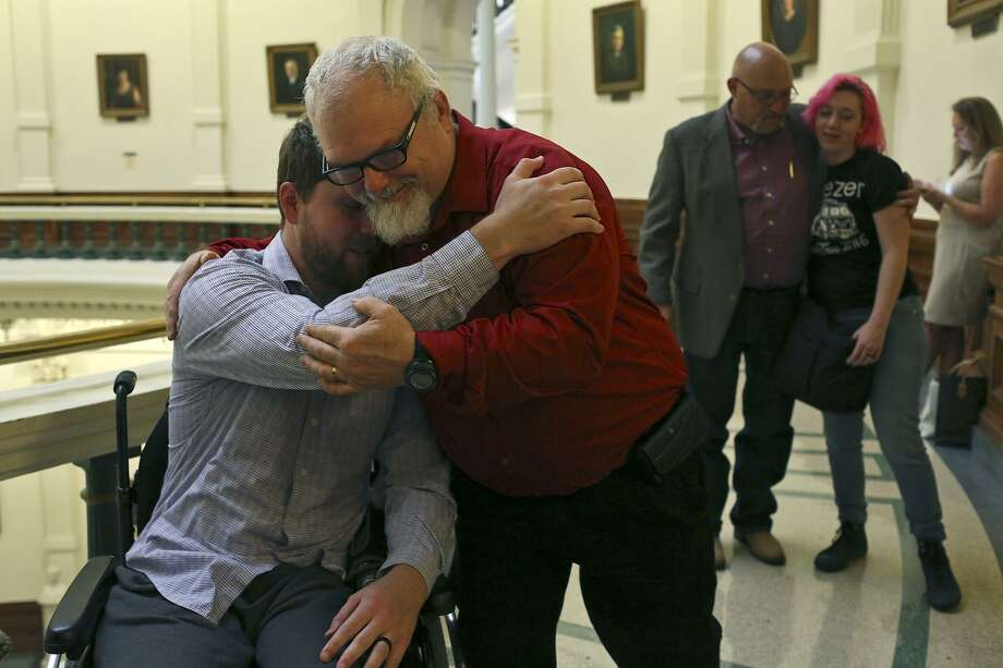 Stephen Willeford, who shot the attacker during the mass shooting at First Baptist Church of Sutherland Springs, embraces Kris Workman, left, who was paralyzed as they arrive to participate in a roundtable with Gov. Greg Abbott concerning school security at the Texas State Capitol on Thursday, May 24, 2018. At right, the church's pastor, Frank Pomeroy, hugs Kris' wife, Colbey Workman. Photo: Lisa Krantz / SAN ANTONIO EXPRESS-NEWS / SAN ANTONIO EXPRESS-NEWS