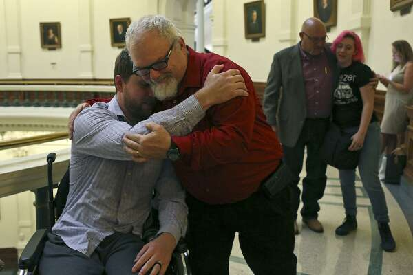 Stephen Willeford, who shot the attacker during the mass shooting at First Baptist Church of Sutherland Springs, embraces Kris Workman, left, who was paralyzed as they arrive to participate in a roundtable with Gov. Greg Abbott concerning school security at the Texas State Capitol on Thursday, May 24, 2018. At right, the church's pastor, Frank Pomeroy, hugs Kris' wife, Colbey Workman.