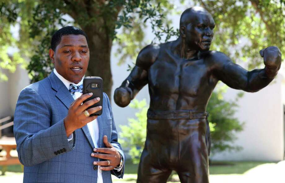 Sam Collins III makes a live social media post as he celebrates President Donald Trump's pardon of Galveston native and boxing legend Jack Johnson in front of a statue of the late boxer at Jack Johnson Park in Galveston, Texas, Thursday, May 24, 2018. (Jennifer Reynolds/The Galveston County Daily News via AP) Photo: Associated Press / © 2018 Jennifer Reynolds/The Galveston County Daily News