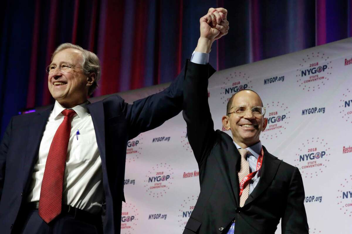 Chairman of the New York Republican State Committee Edward Cox, left, raises the hand of presumptive comptroller candidate Jonathan Trichter at the New York state Republican Convention, in New York, Thursday, May 24, 2018. (AP Photo/Richard Drew)