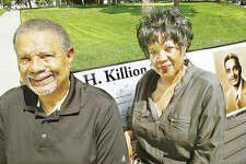 James Killion III and his sister, Carol Killion Hudson, sit on the bench at the corner of the Alton park named after their father, James H. Killion Park at Salu. Their father would have been 100 years old today.