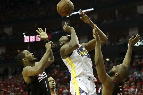 Kevin Durant #35 of the Golden State Warriors goes up against Chris Paul #3 and Trevor Ariza #1 of the Houston Rockets in the third quarter of Game Five of the Western Conference Finals of the 2018 NBA Playoffs at Toyota Center on May 24, 2018 in Houston, Texas.