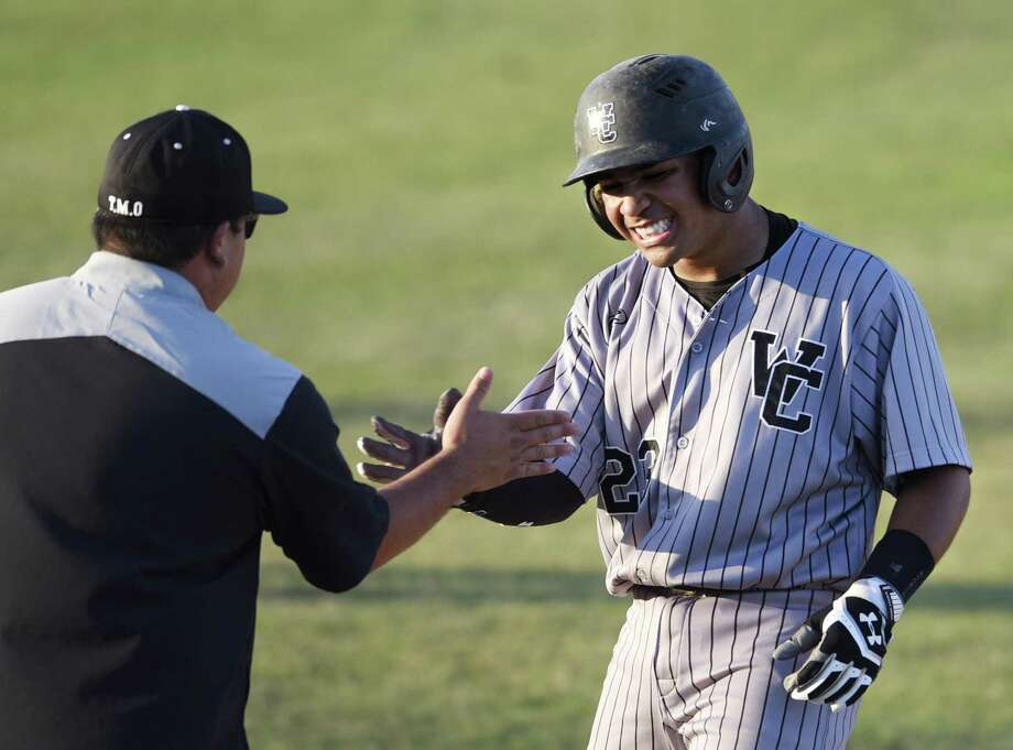 Churchill's Jesse Herrera celebrates with his first-base coach after an RBI single that bounced off the right field fence. Photo: Billy Calzada /San Antonio Express-News / San Antonio Express-News