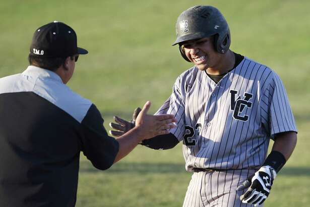 Churchill's Jesse Herrera celebrates with his first-base coach after an RBI single that bounced off the right field fence.