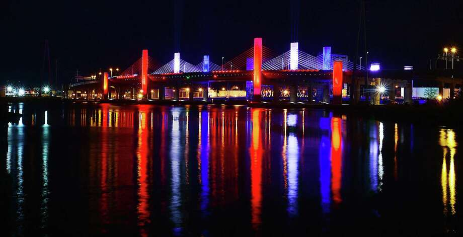 "The Pearl Harbor Memorial Bridge in New Haven, more commonly referred to as the Q Bridge by area residents and resembles a battleship, illuminates the sky in the patriotic colors of red, white and blue, Wednesday, Dec. 6, 2017, marking the surprise attack on the United States Naval Base at Pearl Harbor by the Imperial Japanese Navy Air Service on December 7, 1941. The bombing killed more than 2,300 Americans and destroyed the American battleship U.S.S. Arizona and capsized the U.S.S. Oklahoma. President Franklin Delano Roosevelt called December 7, 1941, ""a date which will live in infamy."" Photo: Catherine Avalone / Hearst Connecticut Media / New Haven Register"
