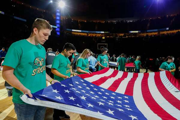 Students from Santa Fe High School hold an American flag during a moment of silence before the first half of Game 5 of the NBA Western Conference Finals at Toyota Center on Thursday, May 24, 2018, in Houston. ( Brett Coomer / Houston Chronicle )