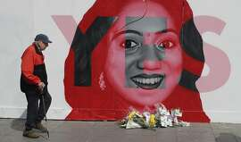 A man walks past a mural showing Savita Halappanavar, a 31-year-old Indian dentist who had sought and been denied an abortion before she died after a miscarriage in a Galway hospital, with the word YES over it, in Dublin, Ireland, on the day of a referendum on the 8th amendment of the constitution. The referendum on whether to repeal the country's strict anti-abortion law is being seen by anti-abortion activists as a last-ditch stand against what they view as a European norm of abortion-on-demand, while for pro-abortion rights advocates, it is a fundamental moment for declaring an Irish woman's right to choose.  (Niall Carson/PA via AP)