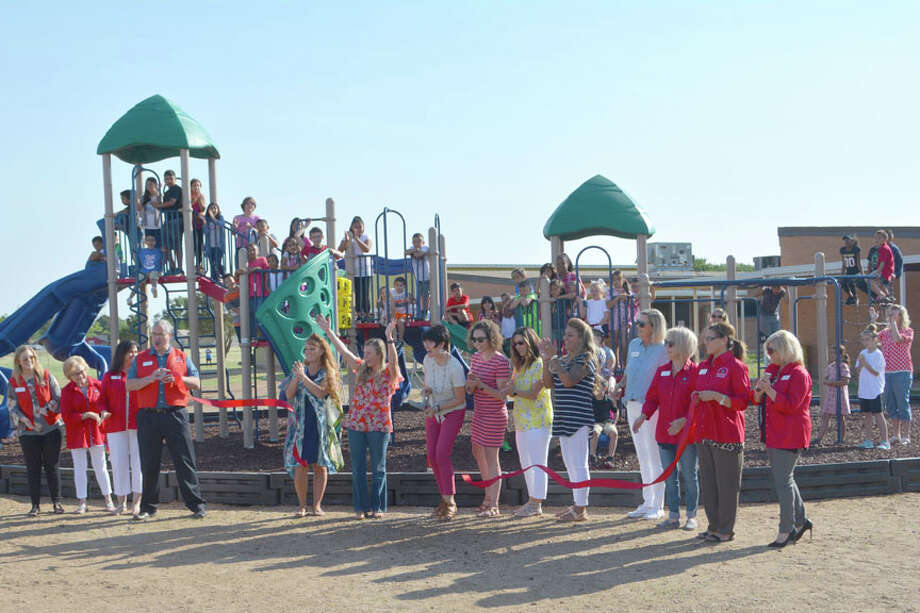 Cheers along with a few hands went up Thursday as College Hill Elementary Principal Lori Glenn cut a ribbon officially opening the new playground at College Hill School. With members of the College Hill PTA and Chamber of Commerce Ambassadors in front, 48 College Hill students – two from each of the school's  24 classrooms – look on while perched on the new equipment. The project was completed late Wednesday afternoon, just in time for the last day of school on Thursday. The new playground was made possible by grants along with community fundraising efforts led by College Hill PTA. Photo: Doug McDonough/Plainview Herald