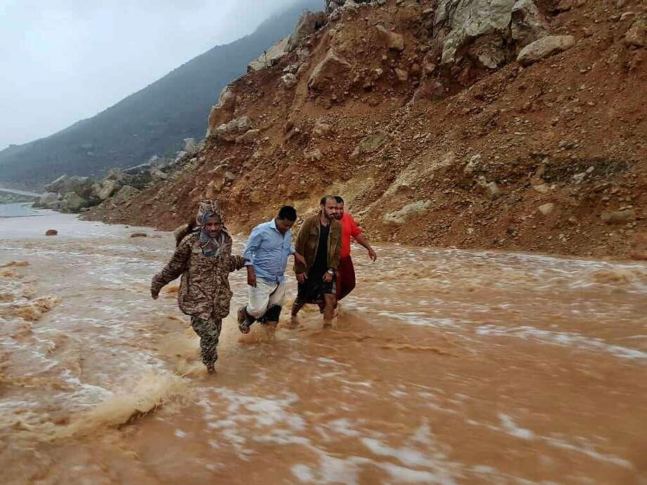 Men wade along a flooded road Thursday in the town of Hadibu on the Yemeni island of Socotra. Cyclone Mekunu is expected to make landfall Saturday near Salalah, Oman. Photo: Abdullah Morgan / Associated Press