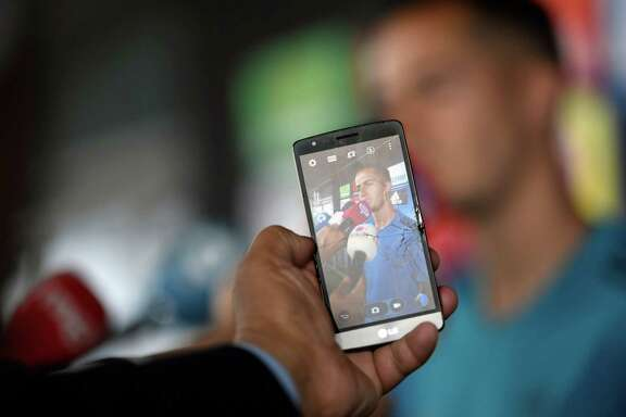 A person takes a photo with a smartphone as Real Madrid's Spanish midfielder Lucas Vazquez addresses journalists during Real Madrid's Media Open Day ahead of their UEFA Champions league final footbal match against Liverpool FC, in Madrid on May 22, 2018.