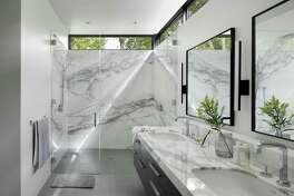 The Calacatta Gold marble walls in this bath are warmer, with stronger veining than Carrera. The bath also has a curb-less, roll-in shower both for continued accessibility as the homeowners age and to eliminate the maintenance associated with a shower curb. The clerestory windows provide both privacy and openings for outside light.