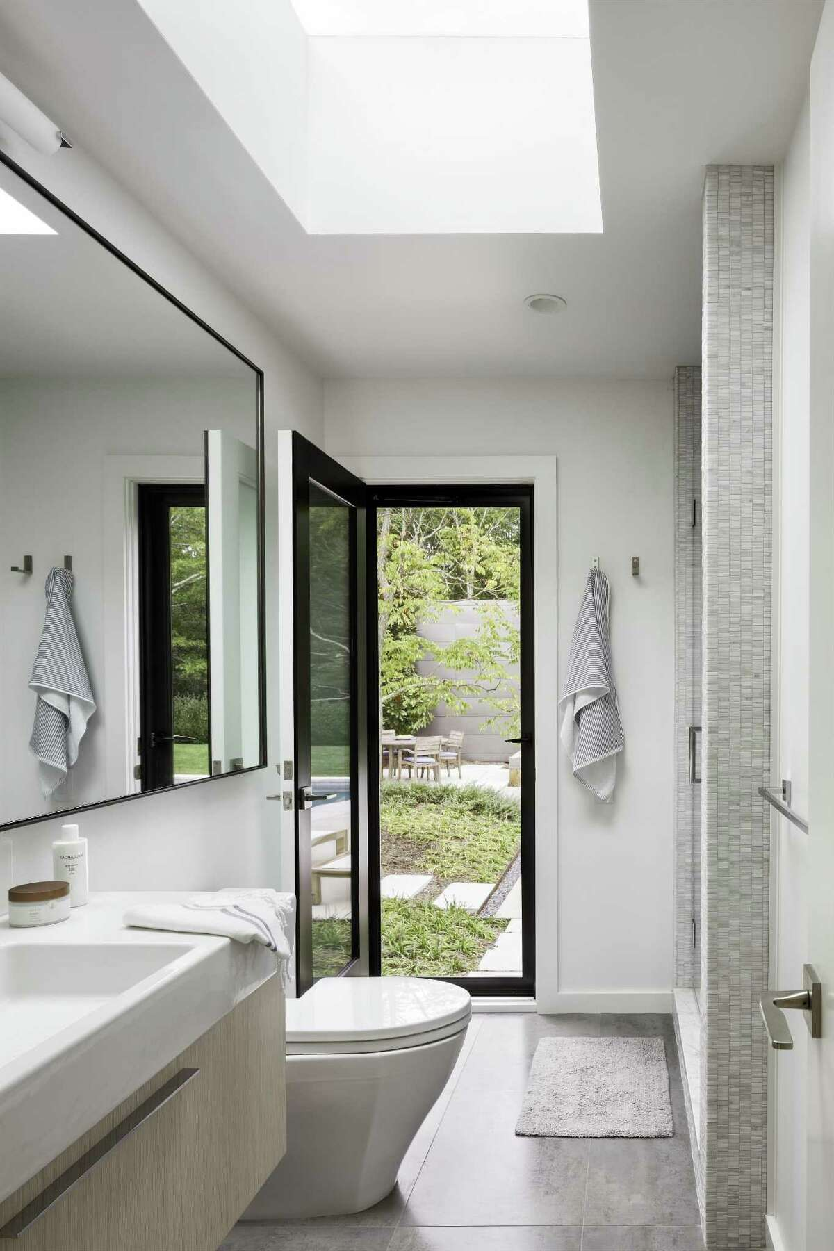 When this master bath was renovated, a door to the backyard was added for easy access outside. The glass door and skylight also allow more light into the relatively small space.