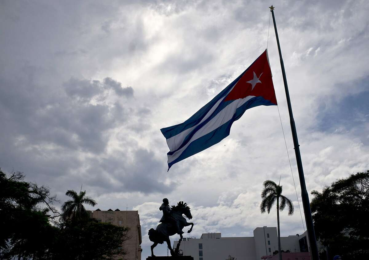 In this Saturday, May 19, 2018 photo, a Cuban flag is seen flying at half-mast near a statue of national hero Jose Marti, marking the start of two days of national mourning, in Havana, Cuba. The Cuban Health Ministry said Friday, May 25, the toll from the crash of the passenger jet in Cuba has risen to 112 after another survivor of the catastrophe died. (AP Photo/Ramon Espinosa)