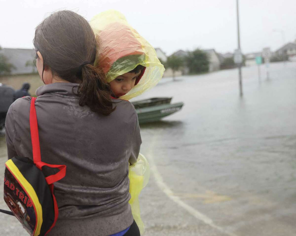 A woman and child who declined to be identified, rest after being rescued from rising flood waters in a neighborhood along Beechnut Road, south of the Barker Reservoir, as heavy rains continue from Tropical Storm Harvey, Monday August 28, 2017, in Fort Bend County.