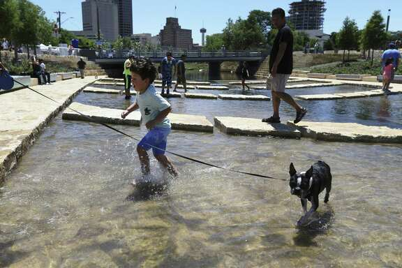 A youngster splashes in the water beside his dog at San Pedro Creek Culture Park in San Antonio. A reader says it makes no sense to allow people to wade in the water, risking the threat of bacterial infection.