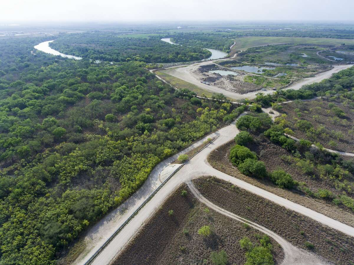 The Rio Grande flows in the background Tuesday, March 27, 2018 near a gap in the border wall in Alamo, Texas. President Donald Trump is expected to visit the area Tuesday to tout his immigration policies.