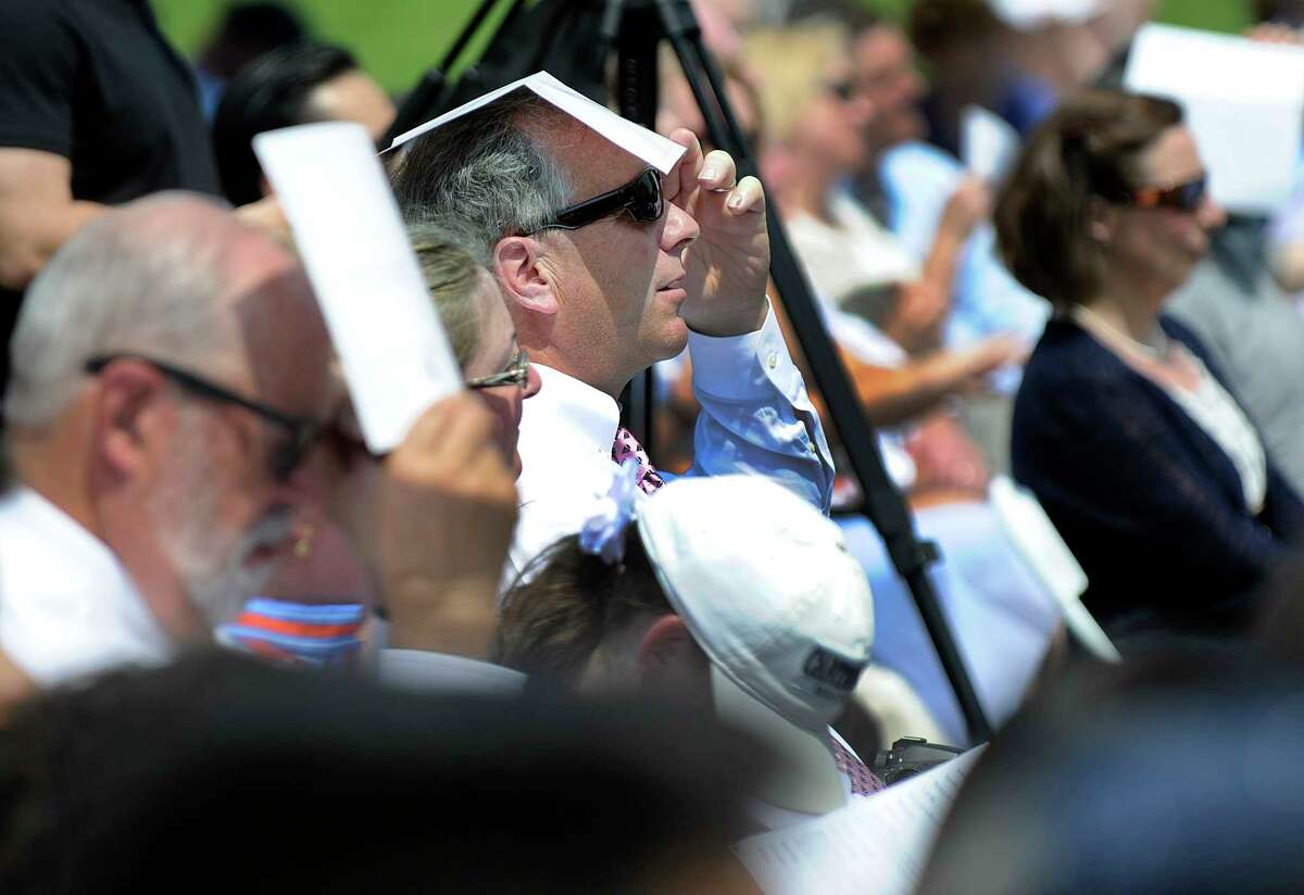 A man shields himself from the sun at Canterbury School in New Milford's graduation ceremony Friday, May 25, 2018.
