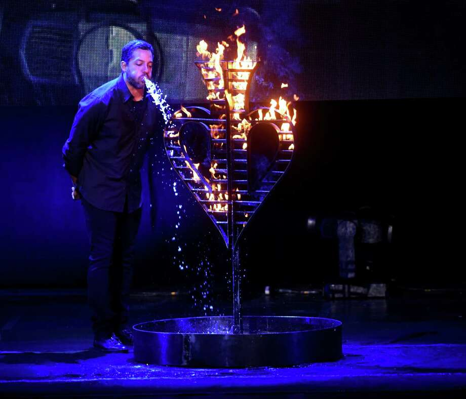 Magician David Blaine puts out a fire by spraying out the copious amount of water that he drank. Photo: Billy Calzada, Staff / San Antonio Express-News / San Antonio Express-News