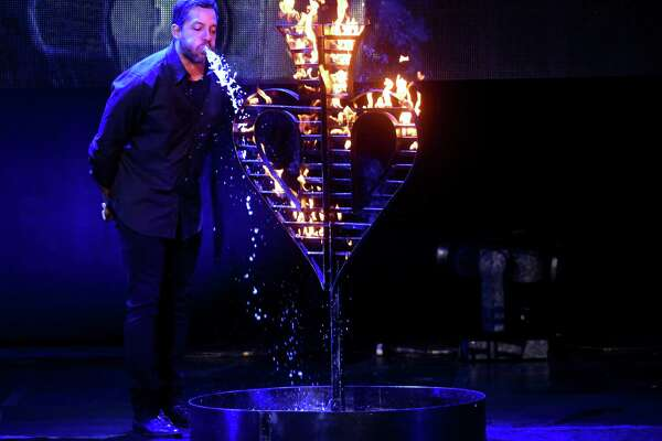 Magician David Blaine puts out a fire by spraying out the copious amount of water that he drank.