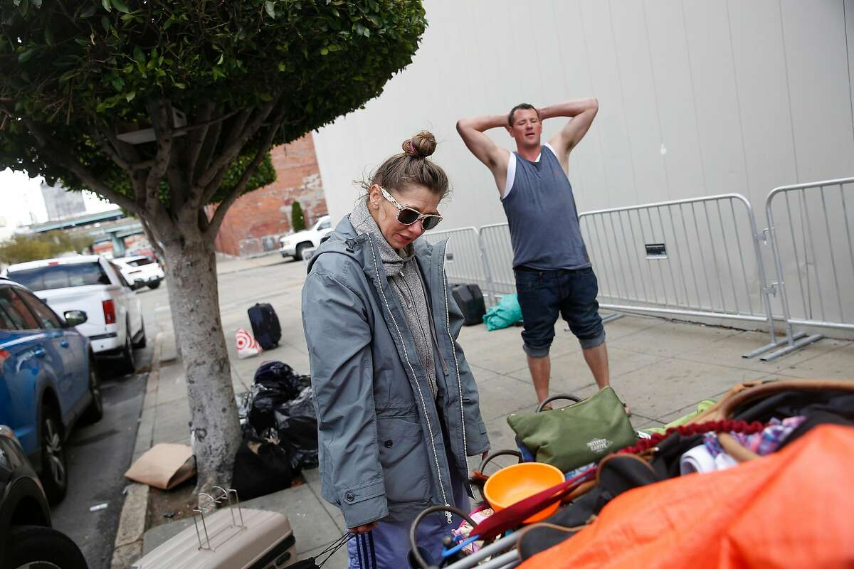 Krystle Erickson (l to r) and Brian Kitchng pack a cart with their belongings as they relocate from Utah Street on Friday, May 25, 2018 in San Francisco, Calif.