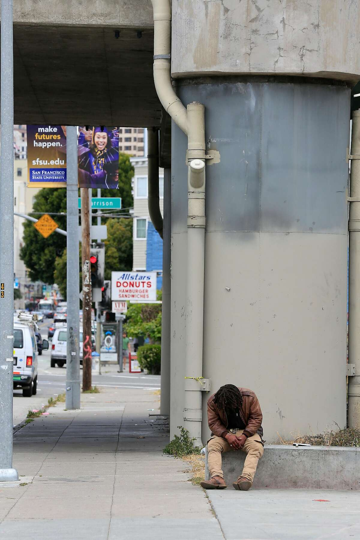 A person sits along 5th Street between Howard and Bryant currently devoid of tents on Friday, May 25, 2018 in San Francisco, Calif.