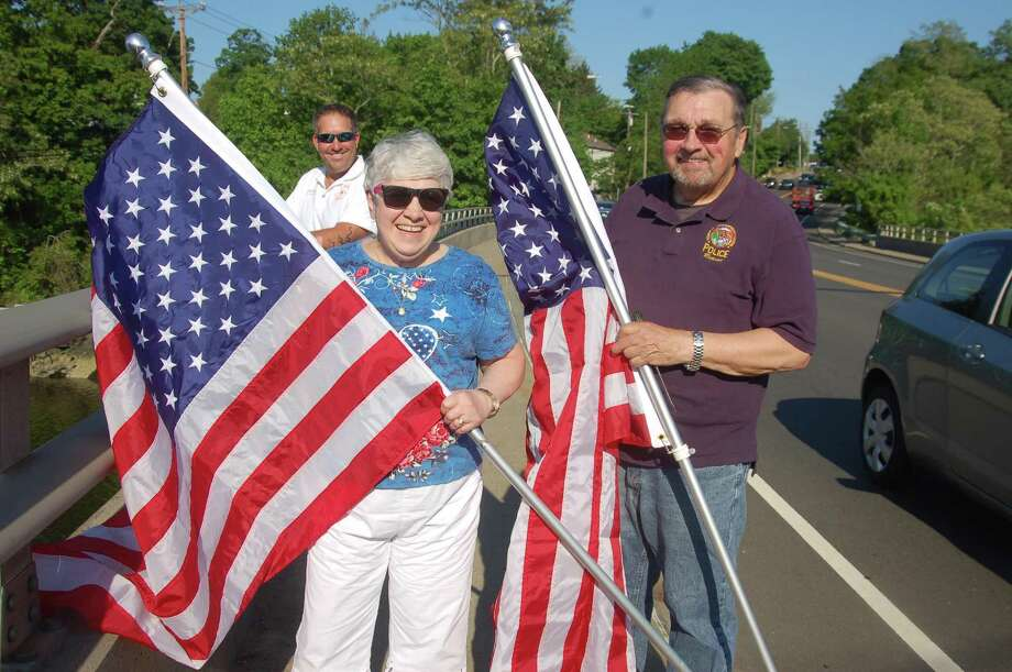 Greenwich residents Barbara and Joseph Havranek standing with the flags they are helping to put up along the bridge. The couple, who are both Air Force veterans, make a donation every year to the Cos Cob Volunteer Fire Company to be able to purchase new flags. Fire company member John Pugni is in the background. Photo: Ken Borsuk