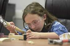 Lilah Reguin, 9, lines up a nail as members of Cub Scout pack 467, from New Milford, completed their Follow the Builder merit badge at Home Depot. The group built a kids workshop wooden classic car kit on Wednesday, May 23, 2018, in New Milford, Conn.