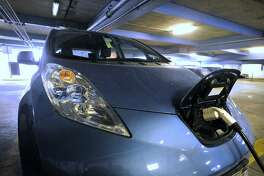 An electric vehicle sits charging at the Bell Street parking garage in Stamford, Conn., on Wednesday, March 5, 2014. Because there is only one electrical hookup at the Bell Street garage, some drivers can't always connect with the electricity.