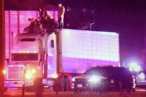 In this screen grab photo taken from a video, authorities surround a tractor trailer with undocumented immigrants standing on the trailer's roof and cab. A total of 86 undocumented immigrants were in the trailer when it was discovered by a trooper from the Department of Public Safety around 8:45 p.m. near Raymondville.