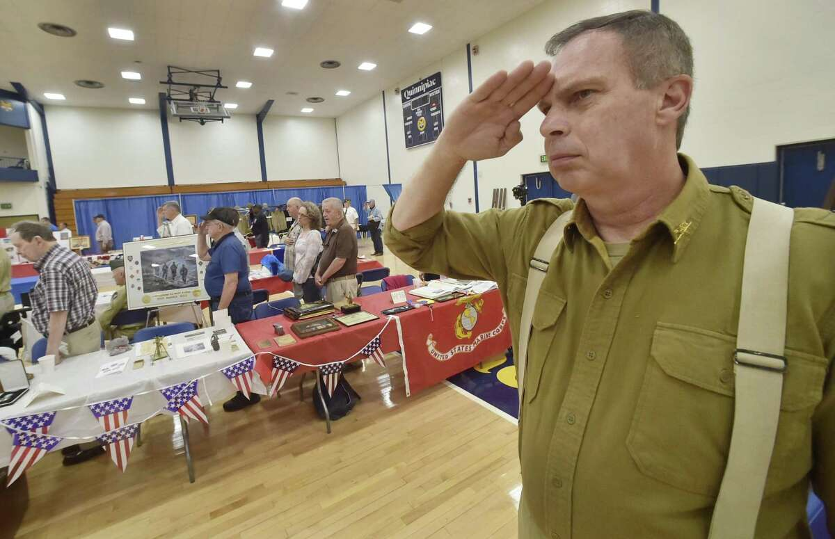 Hamden, Connecticut - May 25, 2018: Mark Wilson of Milford salutes during the National Anthem during the 18th annual Veterans Awareness Day Friday morning at Quinnipiac University in Hamden. The Hamden Veterans Commission sponsors Hamden Veterans Awareness Day. Wilson's exhibit honored World War II U.S. Army Air Force and U.S. Army Airborne Units including the military heritage of his family.