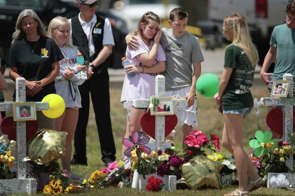 Mourners visit a memorial in front of Santa Fe High School in the wake of the shooting that killed 10 people. A reader says the flood of news stories on such killings serves to motivate would-be shooters.