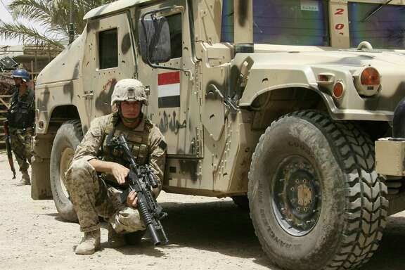 "A U.S. Marine takes cover behind an Iraqi Army humvee during the beginning of combat operations in Amarah, Iraq, 320 kilometers (200 miles) southeast of Baghdad in 2008. Many of these soldiers returned with ""invisible wounds."""