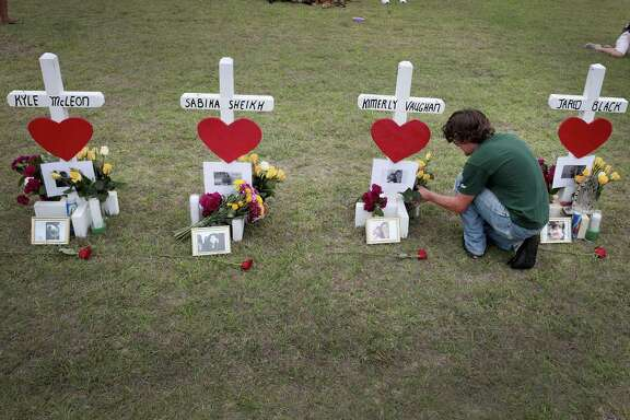 James Otto, a 2011 graduate of Santa Fe High School, leaves flowers at a memorial in front of the school, where 10 people were killed when a teenager with a gun opened fire on them. Our readers continue to discuss the tragedy.