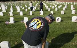 For the 21st year, Bill Strickland was among the volunteers who gather at Hampton National Cemetery in Hampton, Va., Friday morning, May 25, 2018 to place flags at each of the veterans graves. Strickland, a retired Air Force veteran, and other volunteers gathered at Hampton National Cemetery early Friday morning to place the flags at the graves in preparation for Memorial Day weekend. (Bill Tiernan/The Virginian-Pilot via AP)