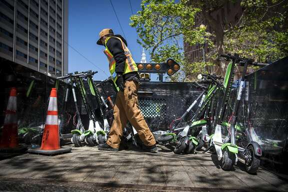 A City of San Francisco Public Works employee loads a Neutron Holdings Inc. LimeBike shared electric scooter onto the back of a truck in San Francisco, California, U.S., on Wednesday, May 2, 2018. City officials, eager to do something about the electric scooters issue, are sending cease-and-desist letters and are planning to require permits soon, while impounding any that they say are parked illegally. Photographer: David Paul Morris/Bloomberg