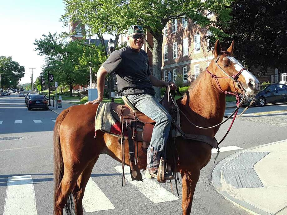 "Dominek Spear and his horse Chrissy took a ride down Main Street in Torrington Thursday night, as the class of 2018 of Northwestern Connecticut Community College was graduating at the Warner Theatre. Spear stopped to speak with a Torrington police officer, who was keeping an eye the street that was closed to traffic for the ceremonies. ""I wanted to see the graduation,"" Spear said with a laugh, before he and Chrissy headed up Main Street. Photo: Emily M Olson / Hearst Connecticut Media"