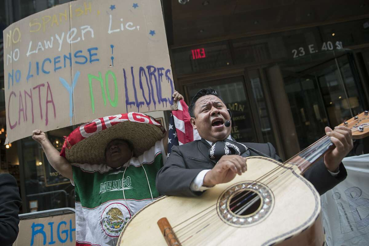 A demonstrator dances and sings along the Mariachi Tapatio de Alvaro Paulino band as they perform during a demonstration across the street from the building that once housed the office space of Aaron Schlossberg, Friday, May 18, 2018, in New York. Schlossberg, a lawyer who was caught on video ranting against Spanish-speaking restaurant workers has been kicked out of his office space and faces a complaint from two elected officials. (AP Photo/Mary Altaffer)