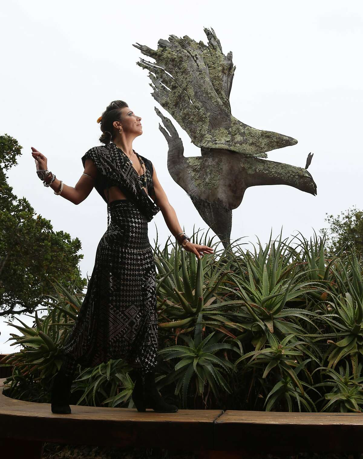 """Rosalia Webster, artist and Big Sur native, photographed near The Phoenix Bird sculpture at Nepenthe restaurant in Big Sur, Calif. on Tuesday, May 22, 2018. The sculpture is the inspiration for much of her art and was made by the famed sculptor Edmund Kara. The performance event, """"Big SurCus,"""" is the brainchild of Webster, a burlesque dancer and performer who has built a show looking back at Big Sur's influence in the Golden Age of Hollywood. It will be staged this summer on the grounds of the Henry Miller Library in Big Sur."""