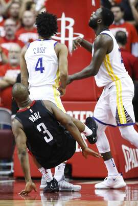 Houston Rockets guard Chris Paul (3) falls to the floor after taking a shot over Golden State Warriors guard Quinn Cook (4) and forward Draymond Green (23) during the second half of Game 5 of the NBA Western Conference Finals against the Golden State Warriors at Toyota Center on Thursday, May 24, 2018, in Houston. Paul suffered a hamstring injury on the play. ( Brett Coomer / Houston Chronicle )