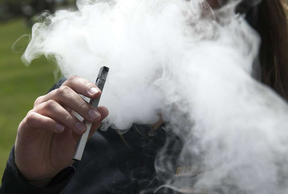 A student of Bishop O'Dowd High School smokes from a Juul e-cigarette at Mountain View Cemetery in Oakland, Calif. Wednesday, May 16, 2018.As soon as next week, FDA Commissioner Scott Gottlieb is expected to announce a ban on the sale of flavored e-cigarettes — the majority of vaping products sold — in tens of thousands of convenience stores and gas stations across the country, according to senior agency officials. Photo: Jessica Christian / The Chronicle