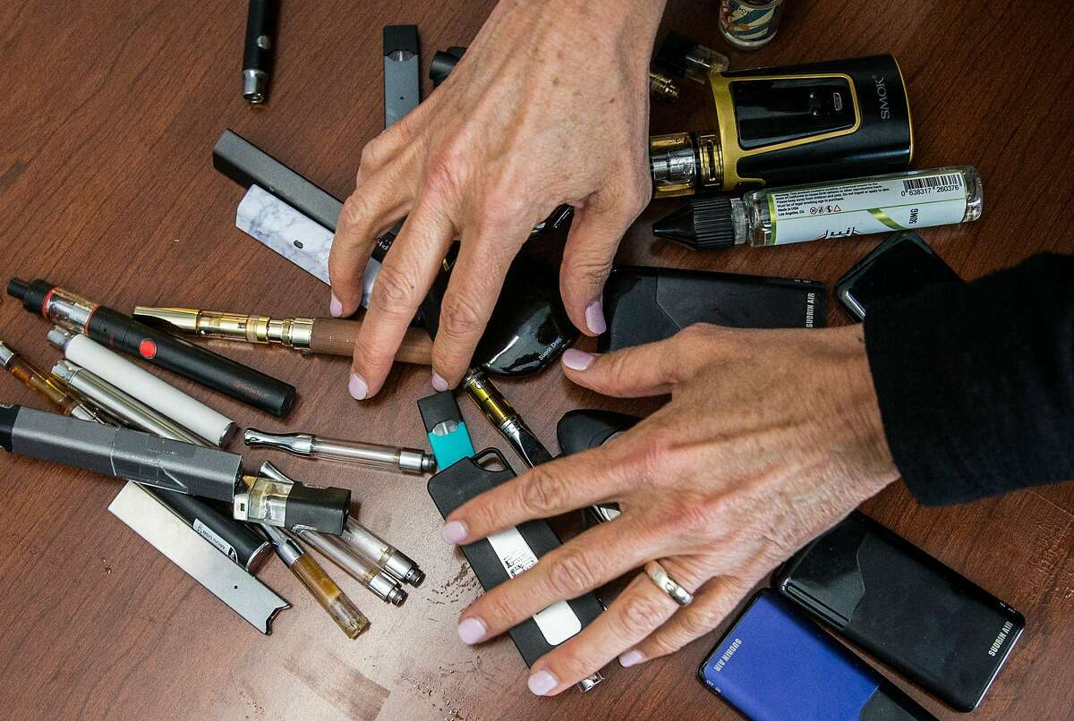 Dublin High School Principal Maureen Byrne sifts through dozens of vaporizer pens, e-cigarettes and Juul branded smoking devices that were confiscated from students at Dublin High School in Dublin, Calif. Wednesday, May 16, 2018.