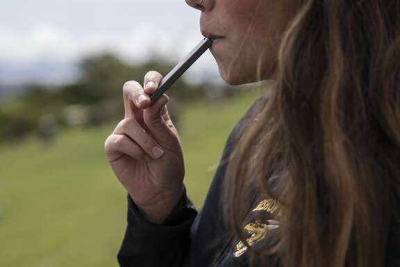 A high school student smokes from a Juul e-cigarette at Mountain View Cemetery in Oakland, Calif. Wednesday, May 16, 2018.