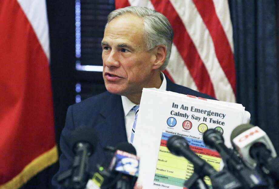 Gov. Greg Abbott presents a school emergency guide Wednesday as he leads a roundtable discussion in the wake of the Santa Fe High School shootings. Photo: Tom Reel, Staff / San Antonio Express-News / 2017 SAN ANTONIO EXPRESS-NEWS
