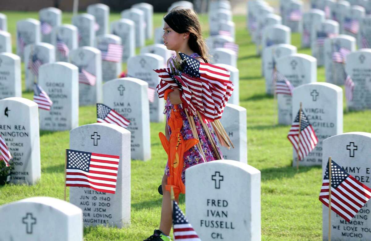 Tabitha Cruz moves across a finished section to meet with her family as scouts and others place flags at gravesites for the Memorial Day weekend on May 25, 2018. Tabitha's grandfather is buried in the cemetery.