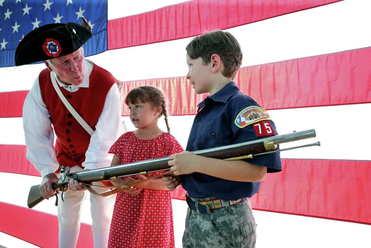 Frank Rohrbough of the Sons of The American Revolution lets siblings Savannah and Ethan Hagan hold his rifle before opening ceremonies as scouts and others place flags at gravesites for the Memorial Day weekend on May 25, 2018.