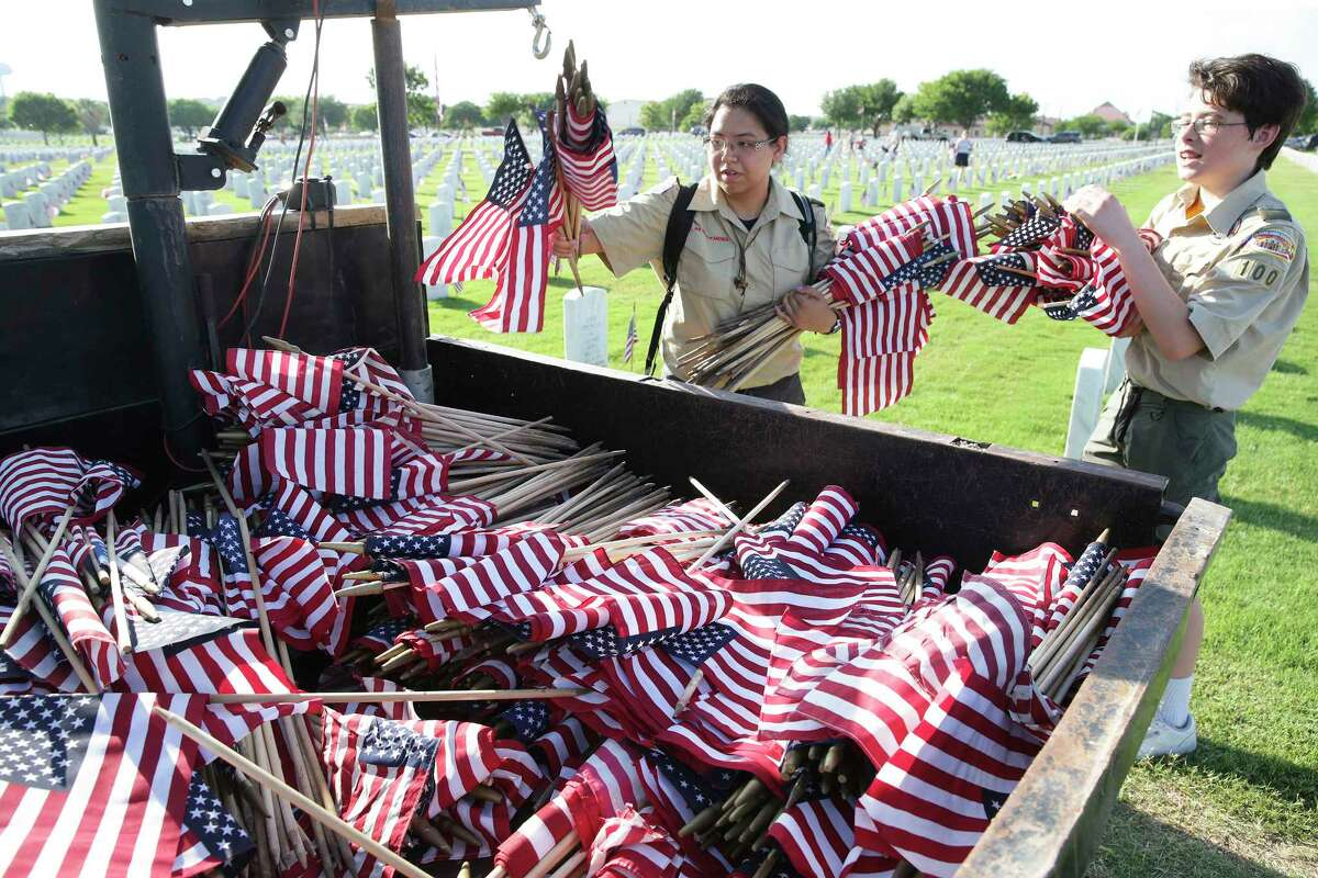 KImberly Vasquez, leader of Boy Scout Troop 100 is assisted by Robert Everts as they replenish their supply of flags as scouts and others place flags at gravesites for the Memorial Day weekend on May 25, 2018.