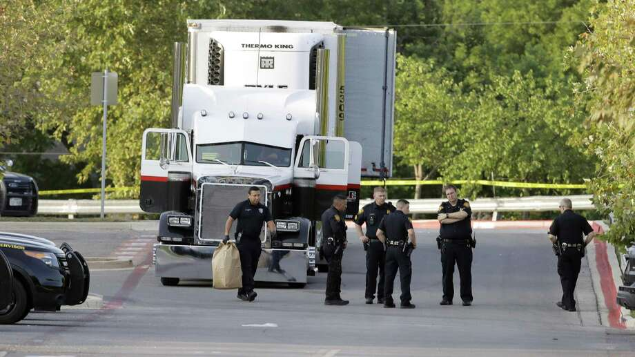 San Antonio police officers investigate the scene Sunday, July 23, 2017, where eight people were found dead in a tractor-trailer loaded with at least 30 others outside a Walmart store in stifling summer heat in what police are calling a horrific human trafficking case,  in San Antonio. (AP Photo/Eric Gay) Photo: Eric Gay, STF / Associated Press / Internal