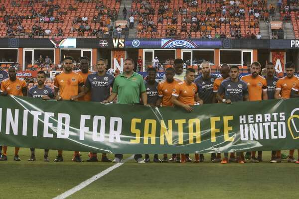"Houston Dynamo and New York City players join to hold a ""UNITED FOR SANTA FE"" banner with Santa Fe Mayor Jason Tabor, center, before kick off the MLS game at BBVA Compass Stadium on Friday, May 25, 2018, in Houston. ( Yi-Chin Lee / Houston Chronicle )"