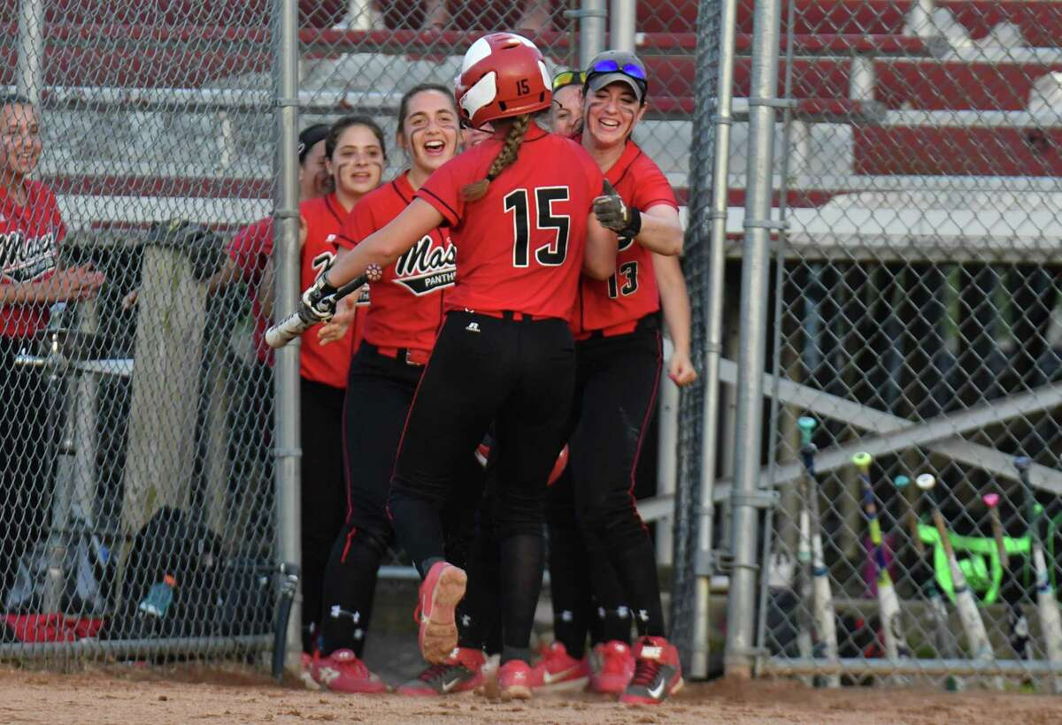 Masuk's Erica Pullen is congratulated by her teammates after scoring the first run during the SWC championship game against Newtown on Friday at DeLuca Field in Stratford.